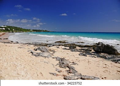 Bermuda beach during a hot summer day.  Photo includes the sky, rocky coastline, pink sand and the tide rolling in.