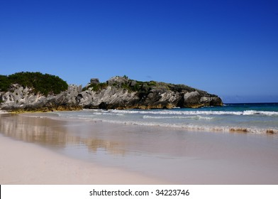 Bermuda's Horseshoe Bay beach during a hot summer day.  Photo includes the sky, large rocks along the coastline, pink sand and the tide rolling in.