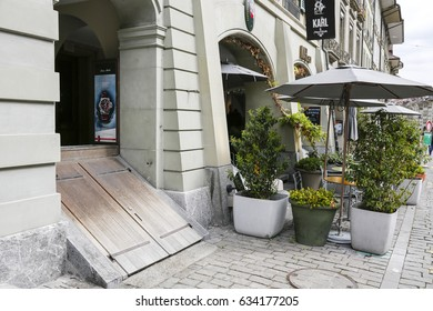 Bern, Switzerland - April 17, 2017: Outside the building the entrance to the basement as detail of the historic architecture of this part of the city and sidewalk cafe can be seen