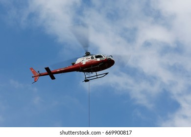 Bern, Switzerland - April 19, 2017: Eurocopter AS350 B3 in colors of a Swiss Helicopter airlines. Machine is at work in a cargo transport operation and hanging rope is a sign that operation is ongoing