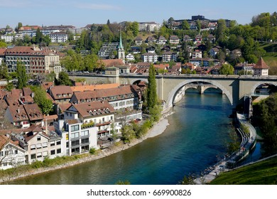 Bern, Switzerland - April 21, 2017: Aare River waters flow through the city. Many townhouses, two bridges and a church tower can be seen