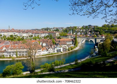 Bern, Switzerland - April 21, 2017: The river Aare flows by the Old Town. The roofs covered with ceramic tiles and stone bridge over the river are recognizable sights of this city