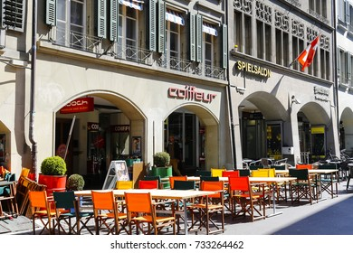 Bern, Switzerland - April 21, 2017: Colorful chairs of outdoor restaurant there are also rectangular tables on a sidewalk next to the building and its arcades.