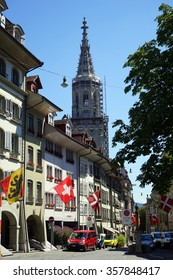 BERN, SWITZERLAND - CIRCA AUGUST 2015 Flags and cars on the street near church