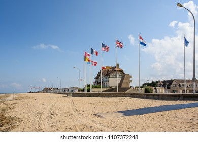"""Bernieres-sur-Mer, Normandy, France - September 2, 2017: Allied flags fly at the monument to the Allied D-Day landings on June 6, 1944, with the historic """"Canada House"""" in the background"""