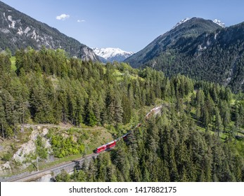 Bernina Express on the railway in a forest, aerial view. Unesco World Heritage