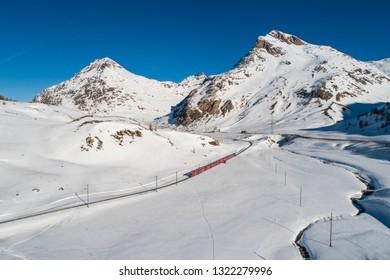 Bernina Express, red train in the winter season. Panoramic view on Bernina Pass
