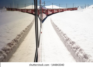 Bernina Express train in the snow with its reflection