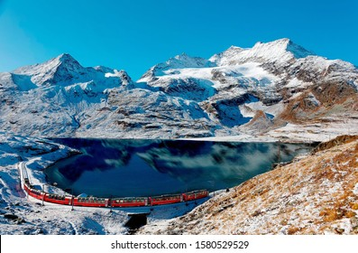 A Bernina Express train travels along the lake shore of Lago Bianco and alpine mountains towering under blue sky in background after a snowfall in autumn, near Ospizio Bernina, in Grisons, Switzerland - Shutterstock ID 1580529529