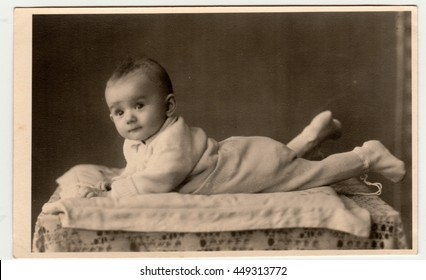 BEROUN, THE CZECHOSLOVAK REPUBLIC - MARCH 1, 1944: Retro photo shows toddler, lie prone. Vintage black & white photography.
