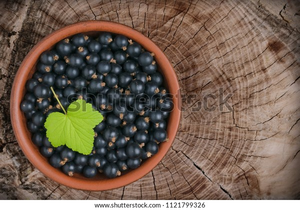 Berries of black currant in a brown ceramic bowl on a wooden background with cracks.