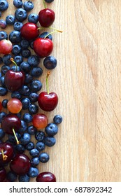 Berries, Cherries, and grapes on wooden background