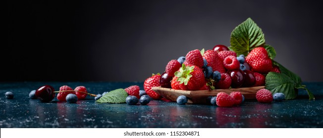 Berries closeup colorful assorted mix of strawberry, blueberry, raspberry and sweet cherry in studio on dark background. - Shutterstock ID 1152304871