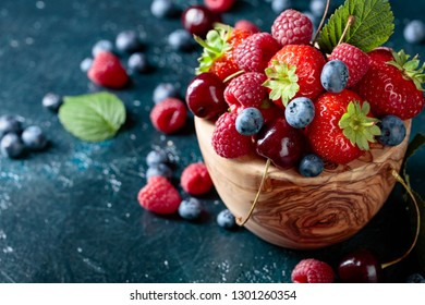 Berries closeup colorful assorted mix of strawberry, blueberry, raspberry and sweet cherry in studio on dark background.