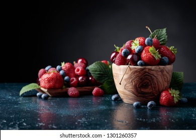 Berries closeup colorful assorted mix of strawberry, blueberry, raspberry and sweet cherry in studio on dark background. Copy space.