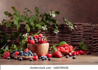 Berries closeup colorful assorted mix of strawberry, blueberry, raspberry and sweet cherry on a old wooden table in garden. Various juicy berries with leaves.
