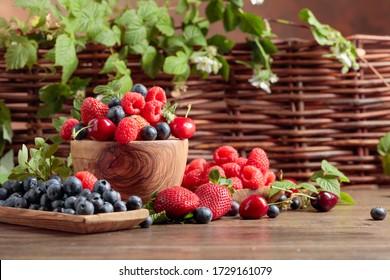古い木のテーブルの上に、イチゴ、ブルーベリー、ラズベリー、甘い桜の混ぜ合わせのベリーの接写。 葉の付いた様々なジューシーなベリー。