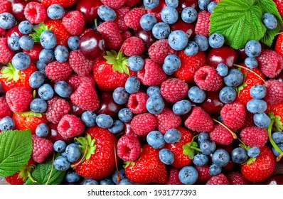 Berries closeup colorful assorted mix of strawberry, blueberry, raspberry and sweet cherry. Top view.