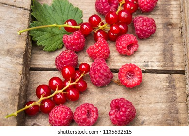 Berries of currants and raspberries on an old board. Red berries on an old board.