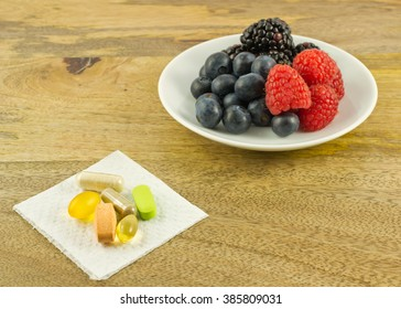 Berries and dietary supplements on wooden table