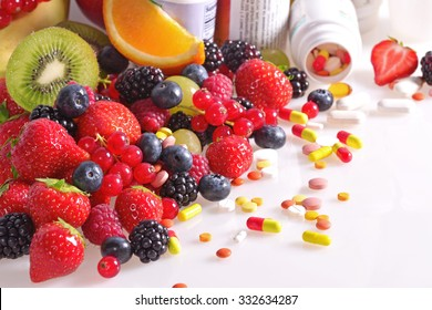 Berries, fruits, vitamins and nutritional supplements on a white background