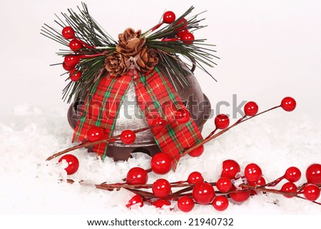 berries and large jingle bell ornament with plaid ribbon with fake snow