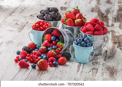 Berries mix blueberry, raspberry, red currant, strawberry, in five old tin cans spilled on white rustic wooden table in studio - Shutterstock ID 707320561