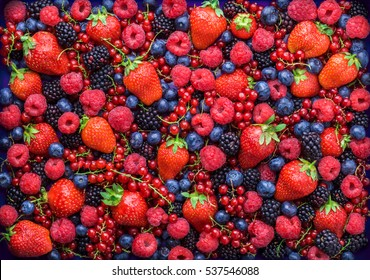 Berries overhead closeup colorful assorted mix of strawberry, blueberry, raspberry, blackberry, red currant in studio on dark background - Shutterstock ID 537546088