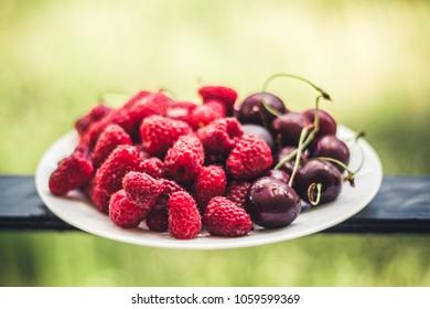berries raspberries and cherries, background blur, on a white plate