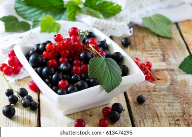 Berries of red and black currant on a wooden background. The concept of a healthy diet and diet.