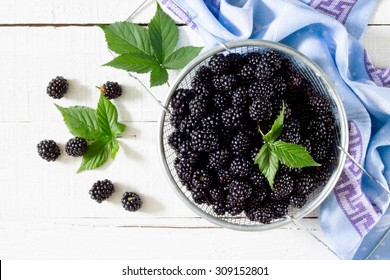 Berries ripe blackberries on a white wooden table, top view.