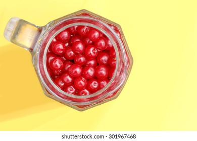 berries ripe cherry in a glass on yellow background
