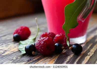Berries of ripe raspberries and black currant on the background of bark