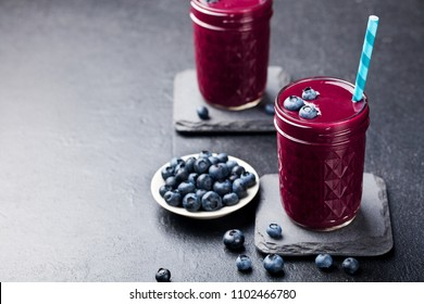 Berry acai smoothie with fresh blueberries on a black stone background. Copy space.