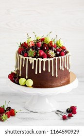 Berry cake with fruit on white cake stand. White background.