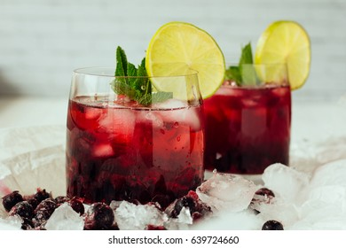 Berry cocktails with mint and lime in glasses selective focus
