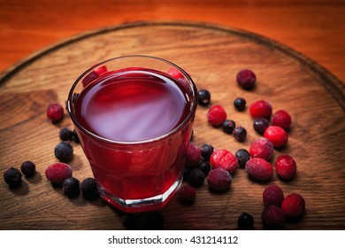 Berry compote in a glass on a wooden board