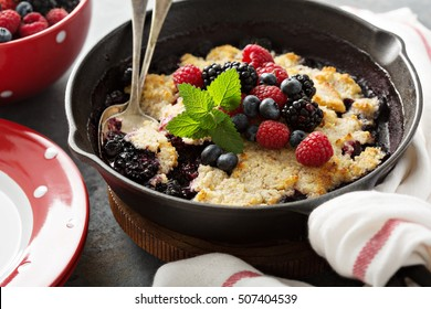 Berry crumble in a cast iron pan with fresh raspberry and blueberry