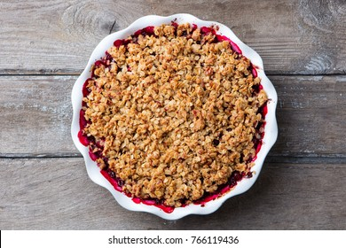 Berry crumble, crisp in baking dish. Wooden background. Top view.
