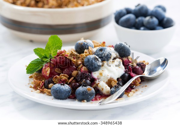 berry crumble with oat flakes and blueberries for breakfast, closeup, horizontal