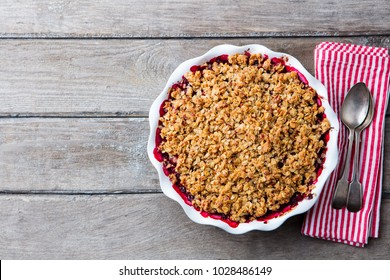 Berry crumble in white baking dish on grey wooden background. Top view. Copy space.
