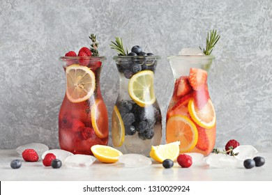 Berry infused water, coctail, lemonade or tea. Summer iced cold drinks with strawberry, blueberry, raspberry, lemon and herbs. Selective focus