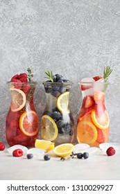 Berry infused water, coctail, lemonade or tea. Summer iced cold drinks with strawberry, blueberry, raspberry, lemon and herbs Selective focus