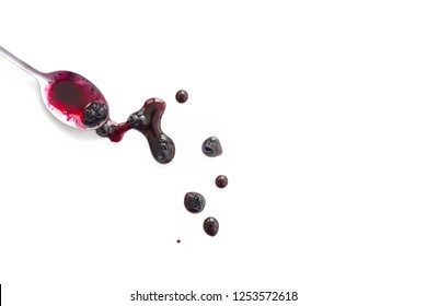 Berry jam splats with spoon isolated on white.