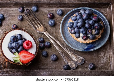 Berry mini tarts with the berries served on coconut over a rustic metal board, top view
