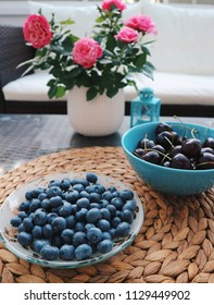 Berry mix in bowls on a table. Blueberries and sweet cherries in a beautiful bowls, roses and candleholder on a table. Side view. Summer, freshness.
