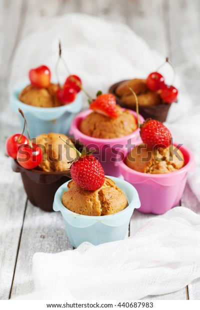 Berry muffins with fresh berries on the old wooden table, close up