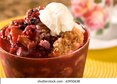 Berry and Peach Cobbler topped with a small scoop of vanilla ice cream.