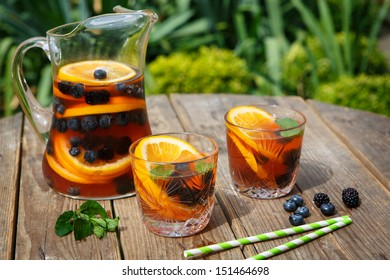 Berry sangria - cold summer cocktail, decorated with berries, orange and mint