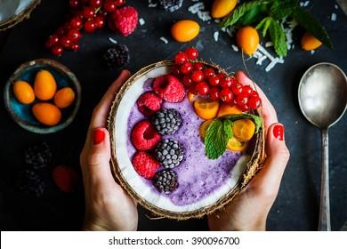 Berry-Smoothie mit Beeren auf Kokosnuss auf rustikalem Hintergrund